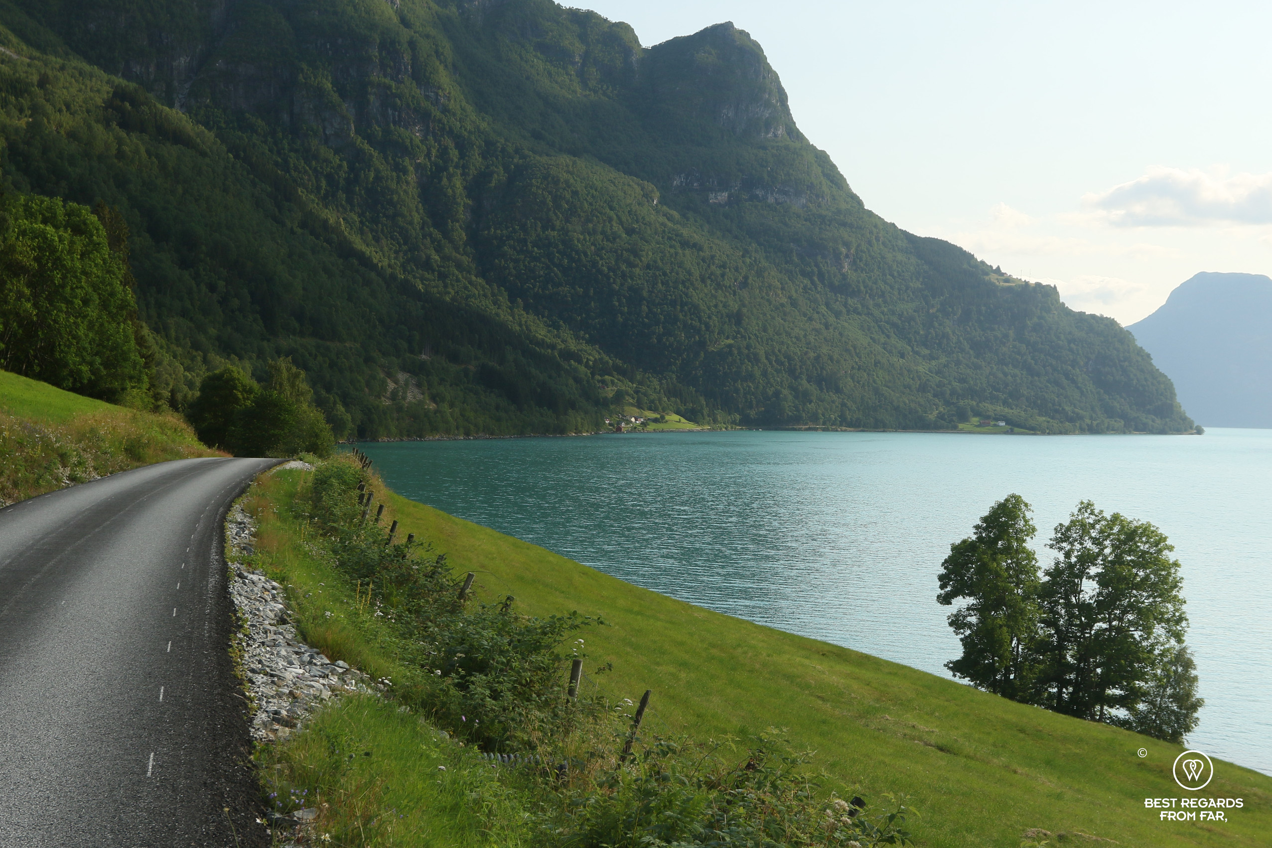 Road leading to Urnes Stave Church between fjord and mountains