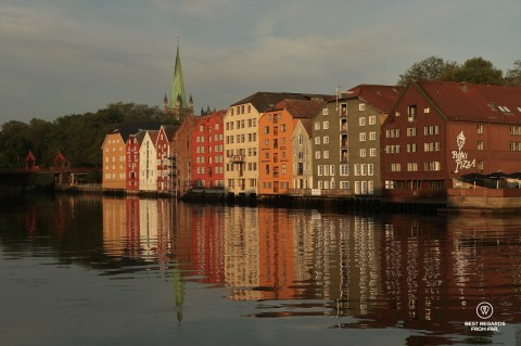 The colourful wood warehouses on stilts of Bryggen in Trondheim reflecting in the water
